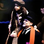 """Philip Paul Kelly as """"Ebenezer Scrooge"""" carrying """"Tiny Tim"""" in """" A Christmas Carol."""""""